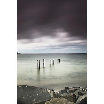 Tre innlegg på rad i det grunne vannet langs kysten under mørke storm cloudsSt marys bay northumberland england PosterPrint