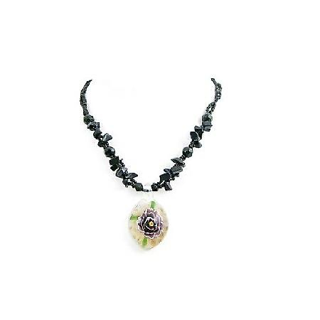 Black Nugget Necklace Holding Glass Pendant That Has Flower Painted